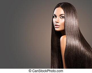 Hermoso cabello largo. Una mujer hermosa con el pelo negro en el fondo oscuro