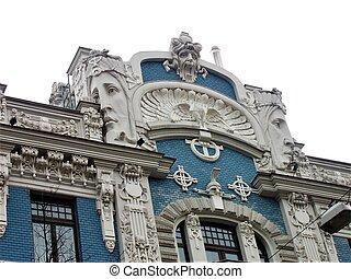 Hermoso edificio de arte con fachada azul y rostros humanos en Riga