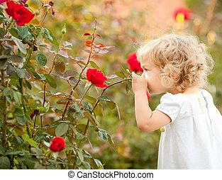 Hermoso niño oliendo a rosa