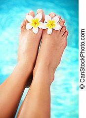 Hermosos pies femeninos y flores tropicales