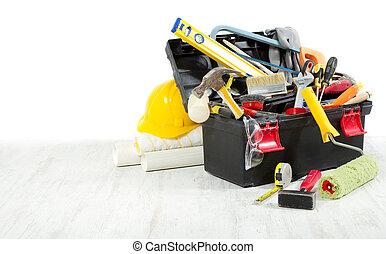 Herramientas en caja de herramientas sobre piso de madera contra pared vacía. Copiar espacio.