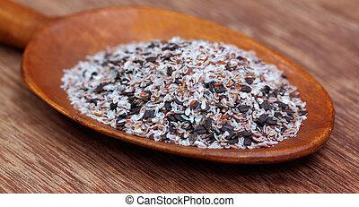 Hierbas medicinales isabgul y semillas de albahaca en una cuchara de madera