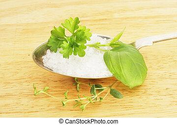 Hierbas y sal en una cuchara de plata