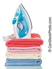 Hierro de vapor moderno y toallas apiladas en blanco.