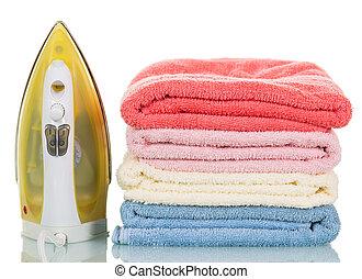 Hierro de vapor moderno y toallas apiladas en fondo blanco.