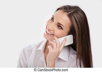 ¡Hola! Una hermosa joven con camisa blanca hablando por teléfono móvil y sonriendo mientras está aislada en blanco