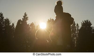 Hombre arrodillado por pareja embarazada al atardecer