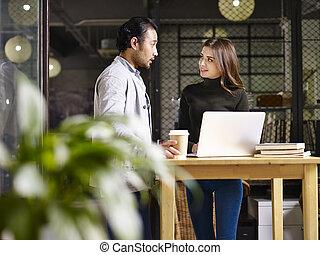 Hombre asiático y mujer caucásica discutiendo negocios en la oficina