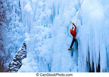 Hombre atlético con abrigo rojo escalando hielo en el desfiladero Incomphagre