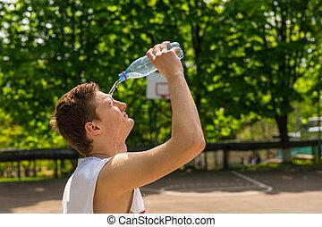 Hombre atlético vertiendo agua de botella en cara