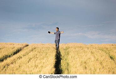 Hombre con brazos extendidos en el campo
