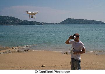 Hombre con cámara drone y gafas de realidad virtual tomando fotos y vídeos en la playa