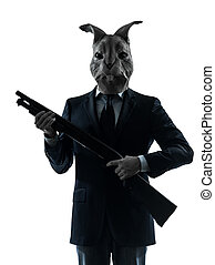 Hombre con máscara de conejo cazando con un retrato de silueta de escopeta