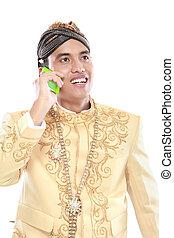Hombre con traje de java tradicional usando teléfono móvil