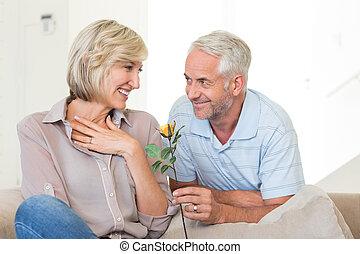 Hombre dando flores a una mujer sonriente sentada en el sofá