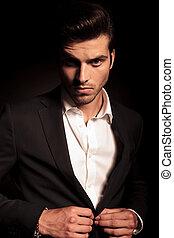 Hombre de la moda abotonando su traje en el fondo negro