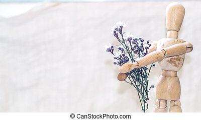 Hombre de madera sosteniendo un ramo de flores