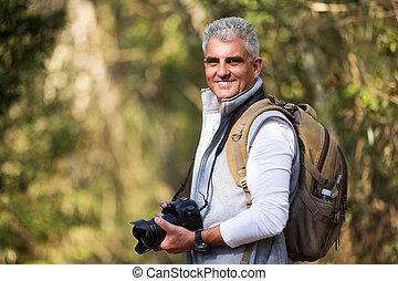 Hombre de mediana edad tomando fotos en la naturaleza