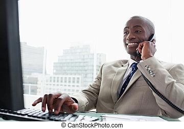 Hombre de negocios al teléfono mientras usa una computadora