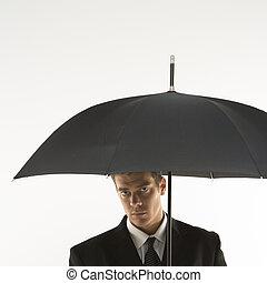 Hombre de negocios bajo paraguas.