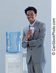 Hombre de negocios bebiendo de un refrigerador de agua en la oficina