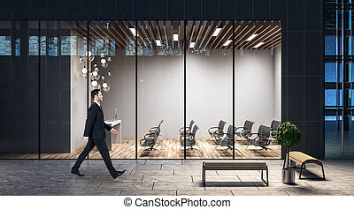 Hombre de negocios caminando por el centro de negocios de la tarde con espaciosa sala de conferencias.