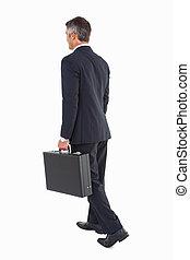 Hombre de negocios caminando y sosteniendo maletín