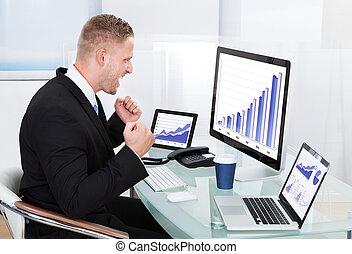 Hombre de negocios celebrando un gráfico de rendimiento