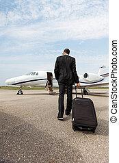 Hombre de negocios con equipaje caminando hacia un jet privado