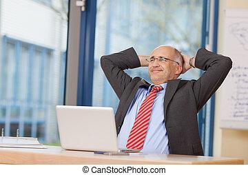 Hombre de negocios con las manos detrás de la cabeza sentado en el escritorio