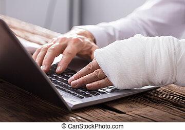 Hombre de negocios con lesión de mano usando portátil