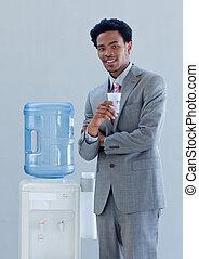 Hombre de negocios con un refrigerador de agua en la oficina