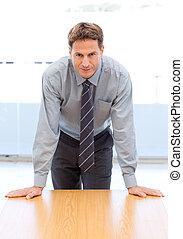 Hombre de negocios confiado posando sobre una mesa