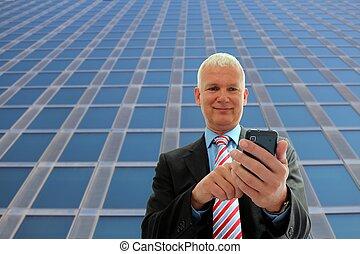 Hombre de negocios escribiendo en su móvil