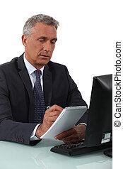 Hombre de negocios escribiendo en un cuaderno