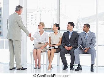 Hombre de negocios estrechando la mano con mujer además de gente esperando una entrevista de trabajo en una oficina brillante