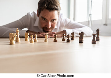 Hombre de negocios mirando piezas de ajedrez en blanco y negro en el escritorio de la oficina