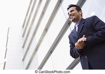 Hombre de negocios parado fuera del edificio de oficinas