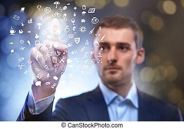 Hombre de negocios pulsando botón con un conjunto de iconos en el aire