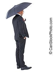 Hombre de negocios refugiado bajo paraguas negro
