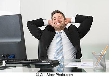 Hombre de negocios relajado con las manos detrás de la cabeza en el escritorio
