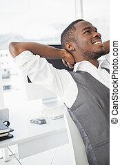 Hombre de negocios relajado con las manos detrás de la cabeza