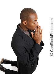Hombre de negocios rezando de rodillas
