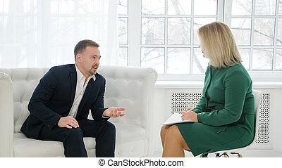 Hombre de negocios sentado en el sofá hablando con la psicóloga femenina