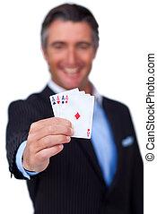 Hombre de negocios sonriente sosteniendo todos los ases