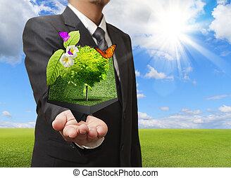 Hombre de negocios sosteniendo una caja creativa de árbol en su mano con pradera verde en el fondo