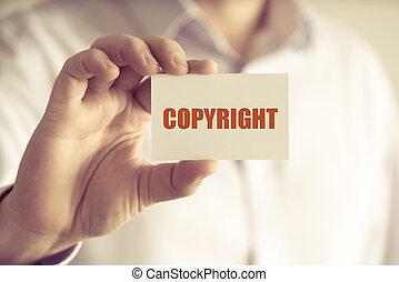 Hombre de negocios sosteniendo una tarjeta de mensaje de Copyright