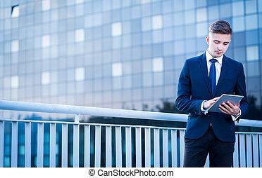 Hombre de negocios usando tablet al aire libre