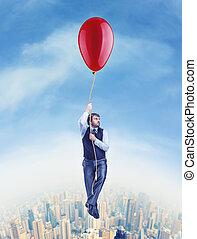Hombre de negocios volando en el gran globo