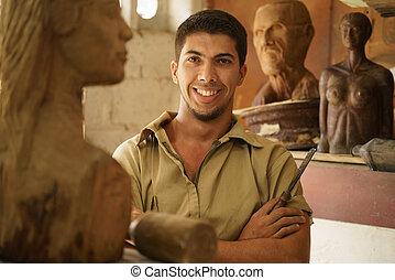 Hombre de retrato que trabaja en una escultura de arte de arte en un taller